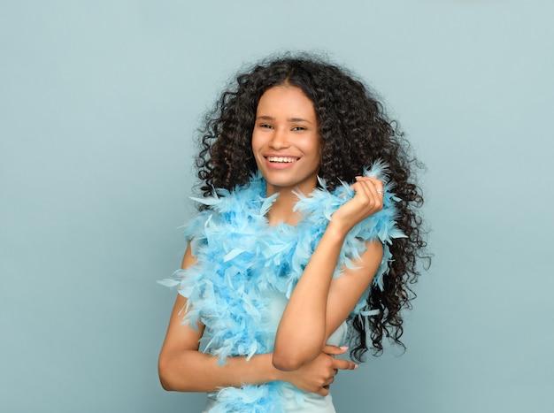 Giovane donna di colore felice in un ritratto di modo sull'azzurro