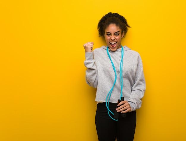 Giovane donna di colore fitness urlando molto arrabbiato e aggressivo. tenendo una corda per saltare.