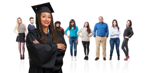 Giovane donna di colore graduata che indossa le trecce che attraversano le sue braccia, sorridenti e felici, essendo sicure e amichevoli