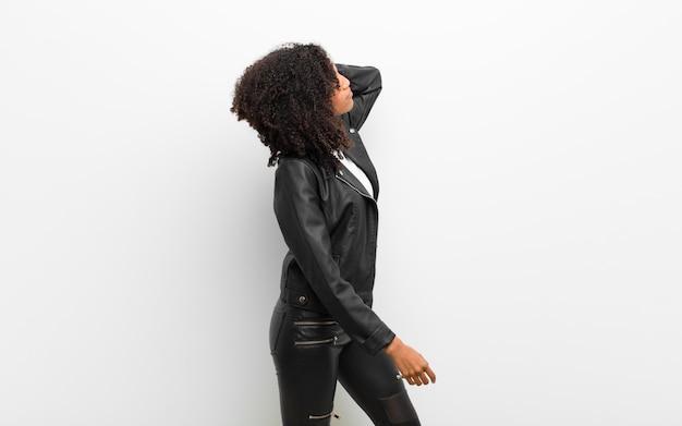 Giovane donna di colore graziosa che indossa una giacca di pelle contro il muro bianco