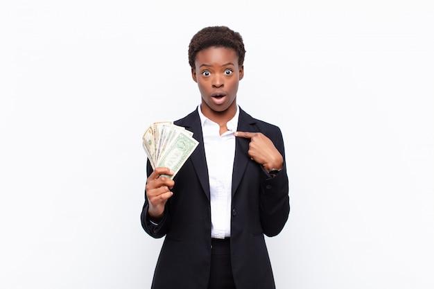 Giovane donna di colore graziosa che sembra scossa e sorpresa con la bocca spalancata, indicando auto con le banconote del dollaro