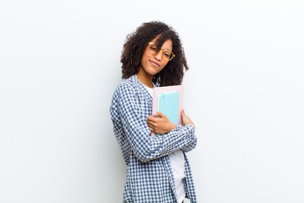 Giovane donna di colore graziosa con i libri contro la parete bianca