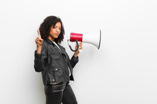 Giovane donna di colore graziosa con un megafono che indossa un muro bianco di giacca di pelle