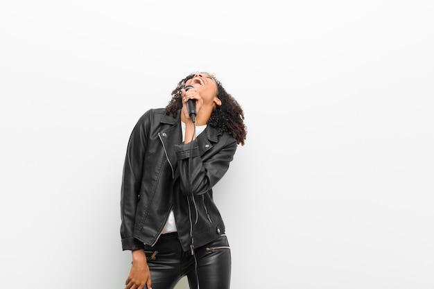 Giovane donna di colore graziosa con un microfono che indossa una giacca di pelle contro il muro bianco