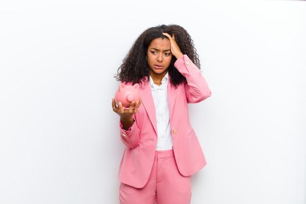 Giovane donna di colore graziosa con un porcellino salvadanaio contro la parete bianca