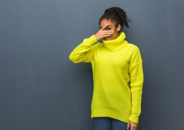 Giovane donna di colore imbarazzata e ridente allo stesso tempo