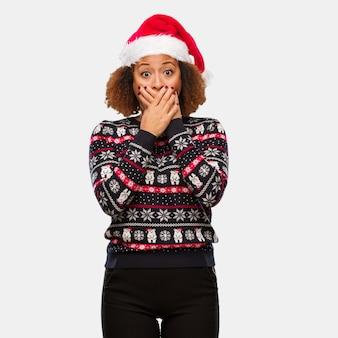 Giovane donna di colore in un maglione di natale alla moda con stampa sorpreso e scioccato