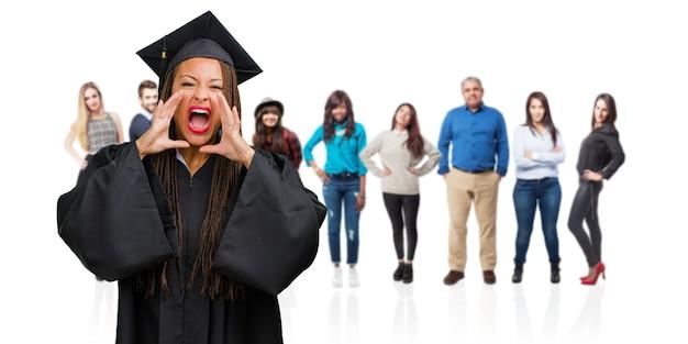 Giovane donna di colore laureata che indossa trecce urlanti arrabbiate, espressione di follia e instabilità mentale, bocca aperta e occhi semiaperti, concetto di pazzia