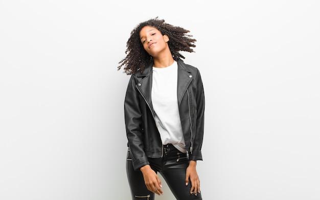 Giovane donna di colore piuttosto ballare indossa una giacca di pelle contro il muro bianco