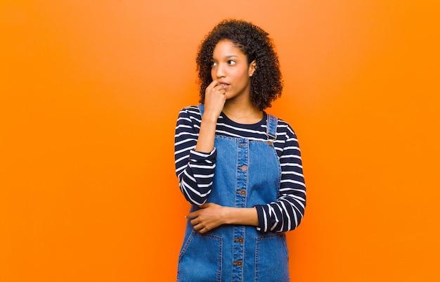 Giovane donna di colore piuttosto con sguardo sorpreso, nervoso, preoccupato o spaventato, guardando al lato verso lo spazio della copia contro la parete arancione