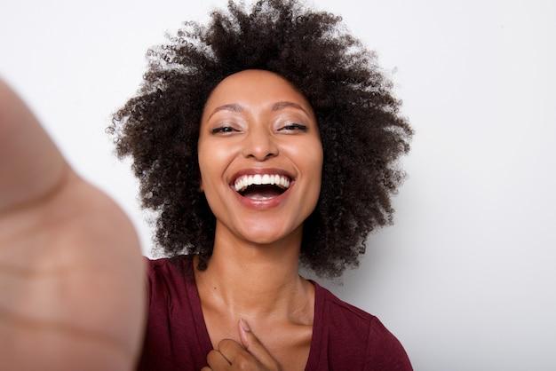 Giovane donna di colore prendendo selfie e ridendo su sfondo bianco