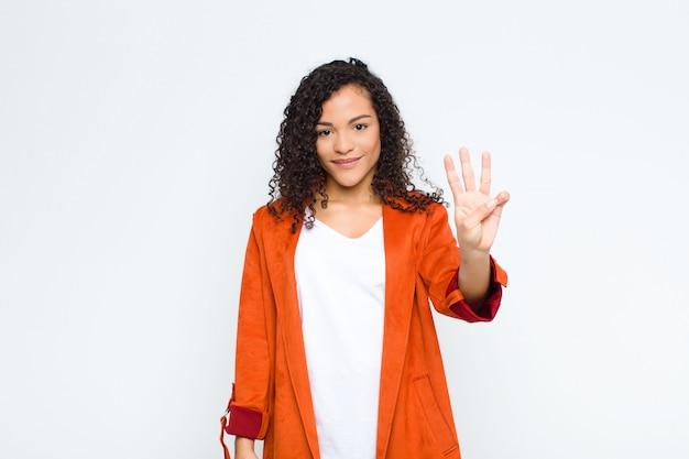 Giovane donna di colore sorridente e dall'aspetto amichevole, mostrando il numero tre o terzo con la mano in avanti, contando alla rovescia contro il muro bianco