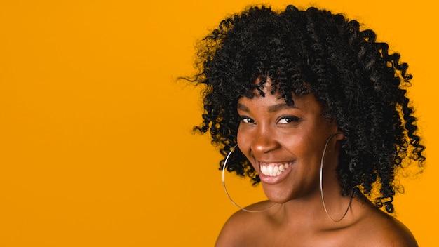 Giovane donna di colore toothy che sorride e che esamina macchina fotografica