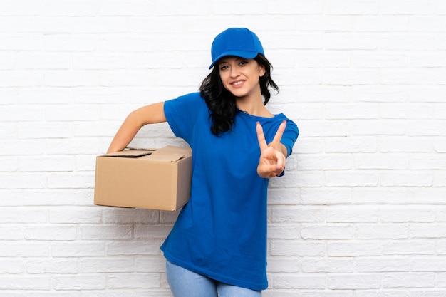 Giovane donna di consegna che sorride e che mostra il segno di vittoria