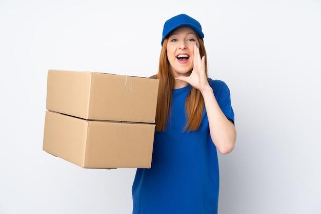 Giovane donna di consegna sopra la parete bianca isolata che grida con la bocca spalancata