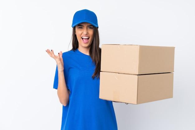 Giovane donna di consegna sopra la parete bianca isolata infelice e frustrata con qualcosa