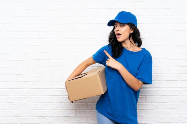 Giovane donna di consegna sul muro di mattoni bianchi sorpreso e indicando il lato