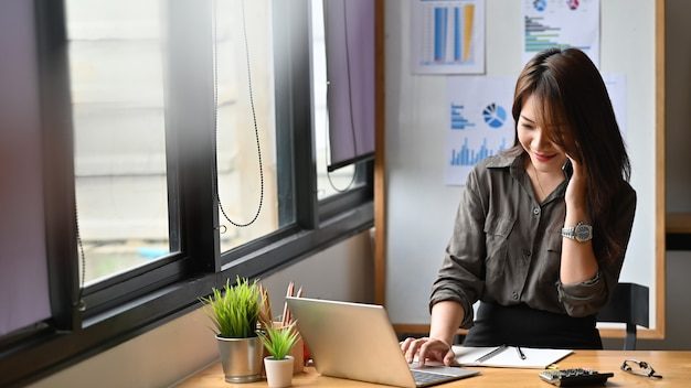 Giovane donna di finanza che rivolge al telefono e che per mezzo del computer portatile.