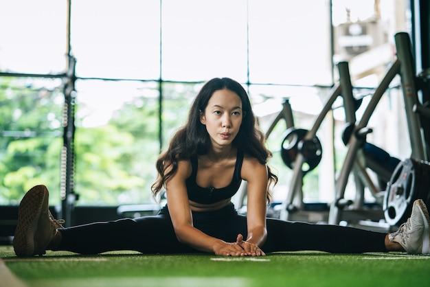 Giovane donna di forma fisica che allunga la sua gamba per riscaldarsi sul pavimento al club di sport della palestra concetto di esercitazione e di allenamento