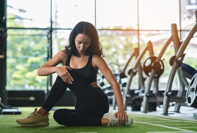 Giovane donna di forma fisica che allunga la sua gamba per riscaldarsi sul pavimento al club di sport della palestra