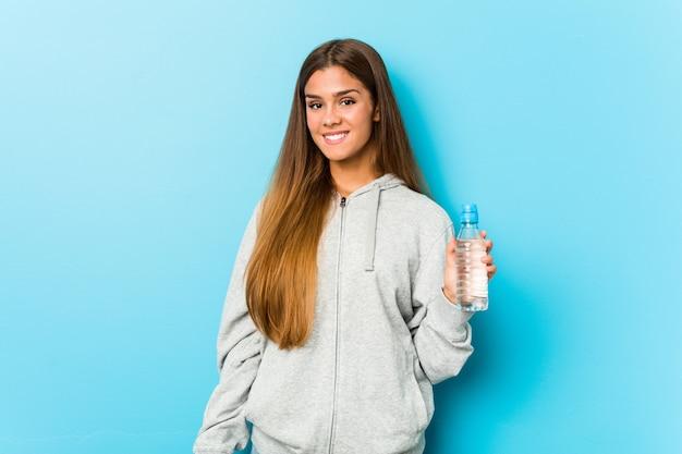 Giovane donna di forma fisica che giudica una bottiglia di acqua felice, sorridente e allegra