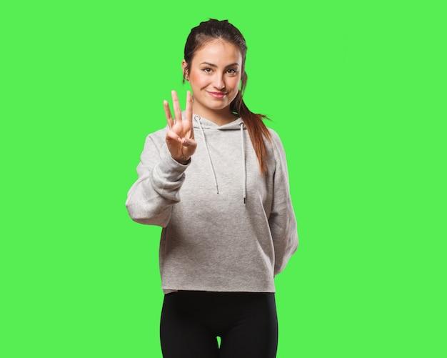Giovane donna di forma fisica che mostra numero tre