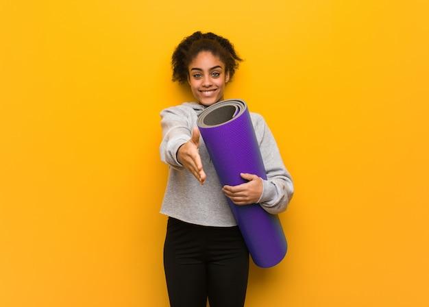 Giovane donna di forma fisica che raggiunge fuori per accogliere qualcuno. in possesso di un tappetino.