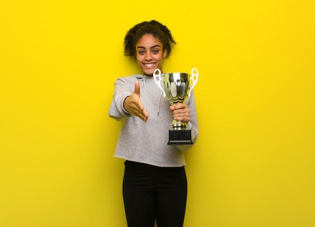 Giovane donna di forma fisica che raggiunge fuori per accogliere qualcuno. in possesso di un trofeo.