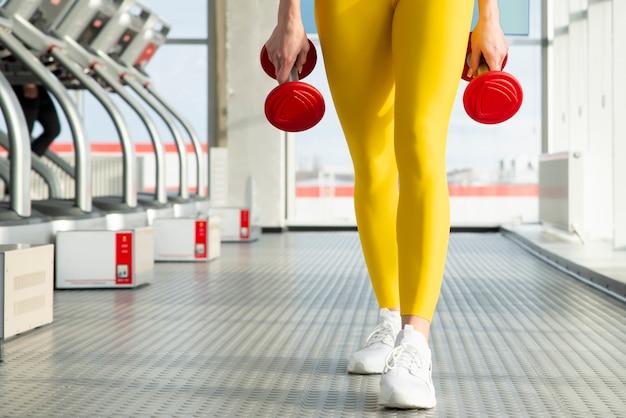 Giovane donna di forma fisica che risolve con la testa di legno in palestra, concetto di sport