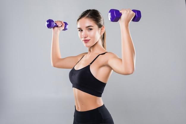 Giovane donna di forma fisica che risolve con la testa di legno isolata sulla parete bianca