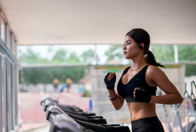 Giovane donna di forma fisica che si esercita con musica d'ascolto e che corre sulla macchina di pedana mobile in palestra
