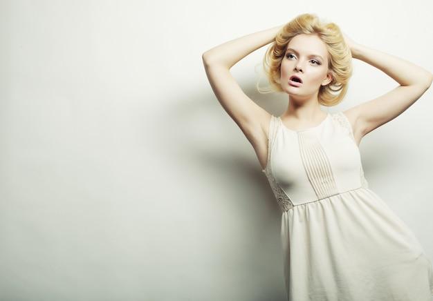 Giovane donna di modo in vestito bianco che posa nello studio