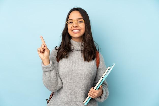 Giovane donna di razza mista che va a scuola sulla parete blu mostrando e sollevando un dito in segno del meglio