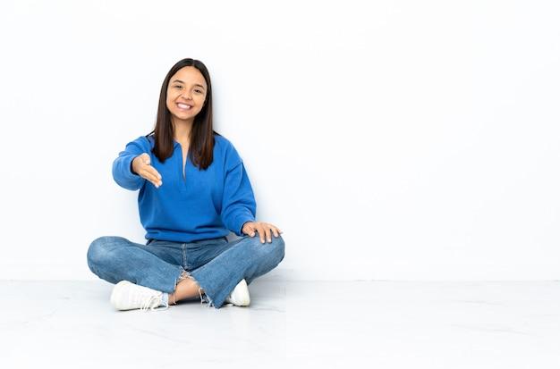 Giovane donna di razza mista seduta sul pavimento sul muro bianco si stringono la mano per chiudere un buon affare