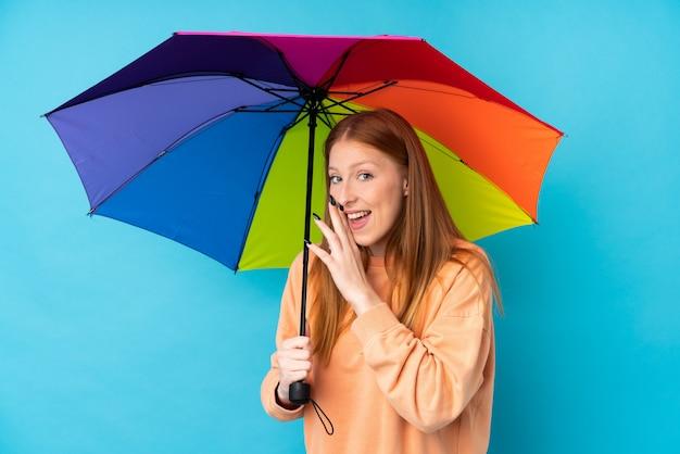 Giovane donna di redhead che tiene un ombrello sopra la parete che bisbiglia qualcosa