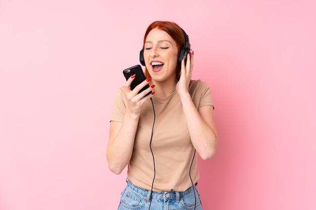 Giovane donna di redhead che usando il cellulare con le cuffie e cantando