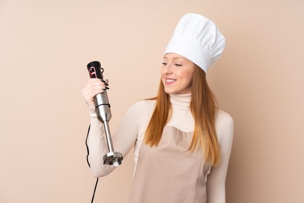Giovane donna di redhead che usando il miscelatore della mano con l'espressione felice