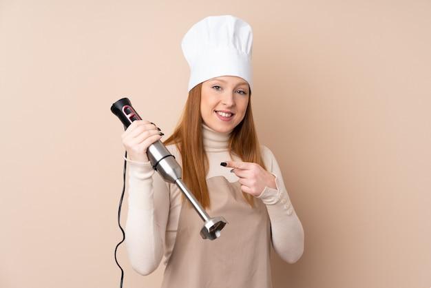 Giovane donna di redhead che usando il miscelatore della mano e indicandolo
