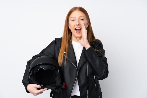 Giovane donna di redhead con un casco del motociclo che grida con la bocca spalancata