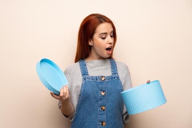 Giovane donna di redhead isolata sopra tenendo un regalo in mano