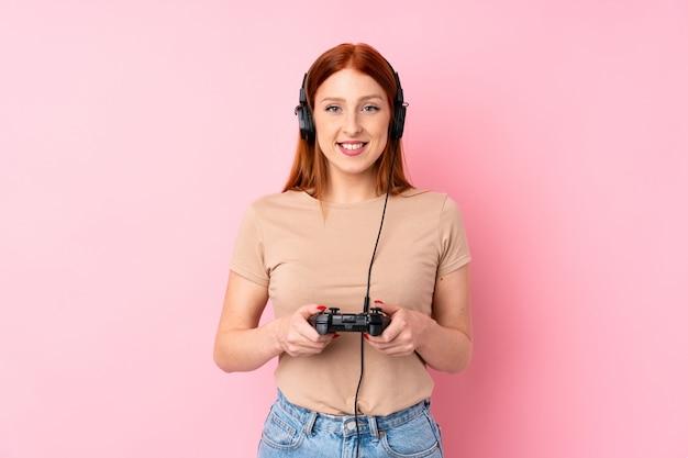 Giovane donna di redhead sopra la parete rosa isolata che gioca ai videogiochi