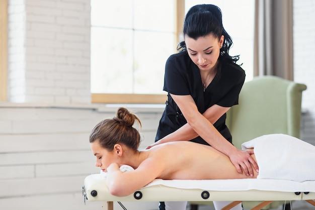 Giovane donna di rilassamento che ha massaggio sulla parte posteriore nel salone della stazione termale.