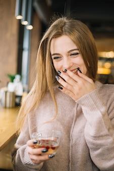 Giovane donna di risata elegante con la tazza della bevanda in caffè