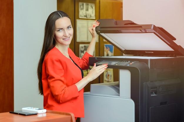 Giovane donna di segretaria che fa le fotocopie all'ufficio.