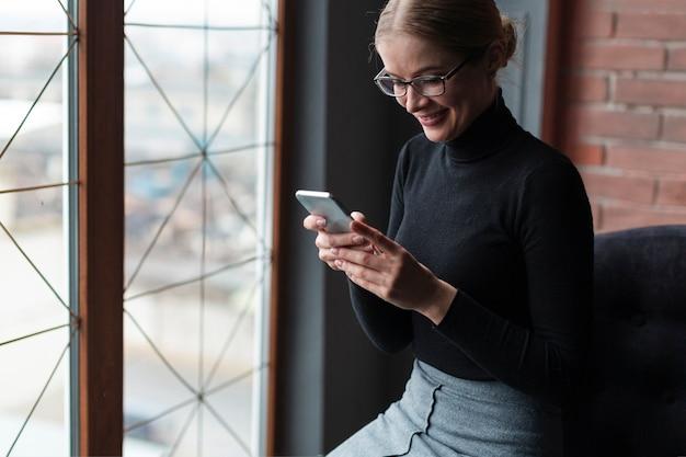 Giovane donna di smiley che per mezzo del telefono