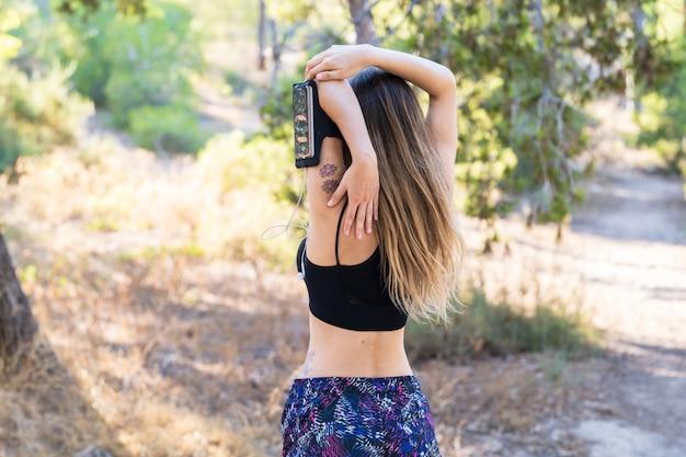Giovane donna di sport che allunga in un parco all'aperto