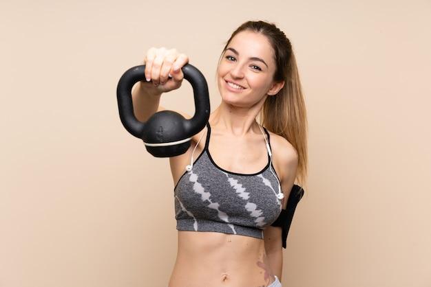 Giovane donna di sport che fa sollevamento pesi con un kettlebell