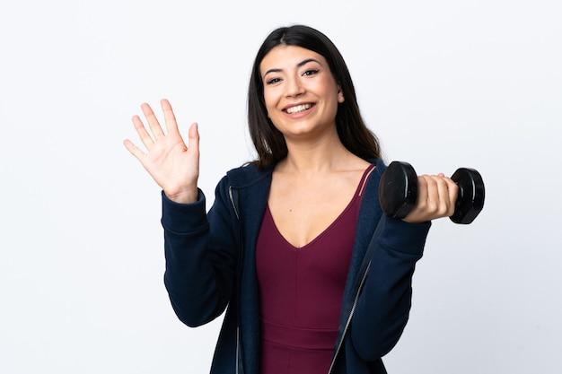 Giovane donna di sport che fa sollevamento pesi sopra la parete bianca che saluta con la mano con l'espressione felice