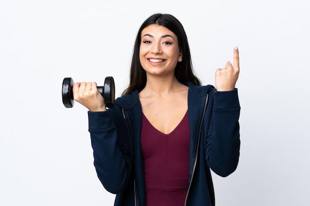 Giovane donna di sport che fa sollevamento pesi sopra la parete bianca isolata che indica su una grande idea