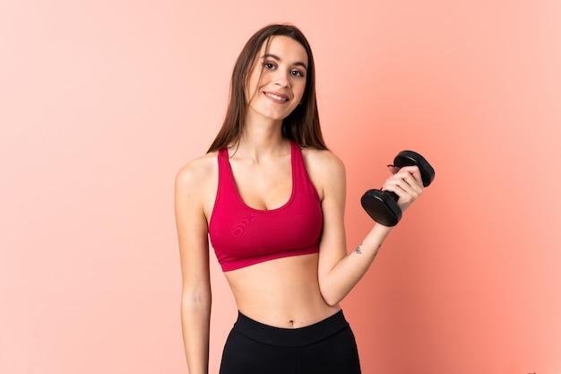 Giovane donna di sport che fa sollevamento pesi sopra la parete rosa isolata con l'espressione felice